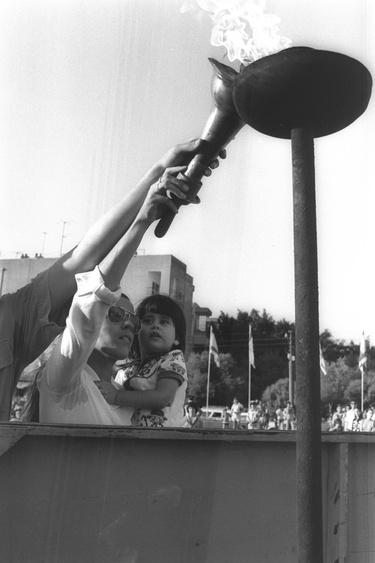 Wdowa po zmarłym Andre Spitzerze, jednym z 11 atletów zamordowanych w Monachium, trzymając swoją córkę zapala znicz olimpijski podczas uroczystości upamiętniającej na Yud Alef. Fot. Yaakov Saar, Government Press Office (Israel), [CC BY-SA 3.0](https://creativecommons.org/licenses/by-sa/3.0/deed.pl)