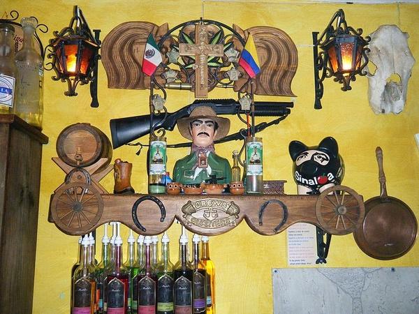 """Jesús Malverde, nieformalny patron _narcos_, jego kult nie jest uznawany przez żaden kościół chrześcijański, jednak cieszy się dużą popularnością m.in. w stanie Sinaloa. Wykorzystane na """"ołtarzu"""" symbole chrześcijańskie mieszają się z atrybutami karteli narkotykowych. Taki kult dobrze oddaje nastawienie części społeczeństwa do handlarzy narkotykami (fot. Marrovi, udostępniono na licencji: [Creative Commons Attribution-Share Alike 3.0 Unported](https://creativecommons.org/licenses/by-sa/3.0/deed.en))"""