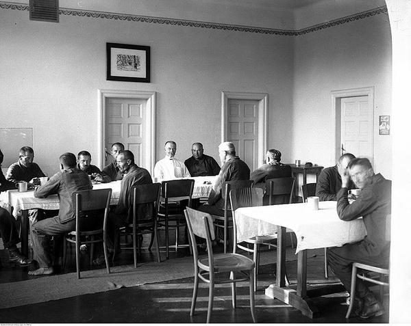 Pacjenci ośrodka w Kobierzynie w jadalni podczas spożywania posiłku. Wśród nich widoczny dyrektor szpitala doc. dr med. Juliusz Morawski, sierpień 1927 r., domena publiczna