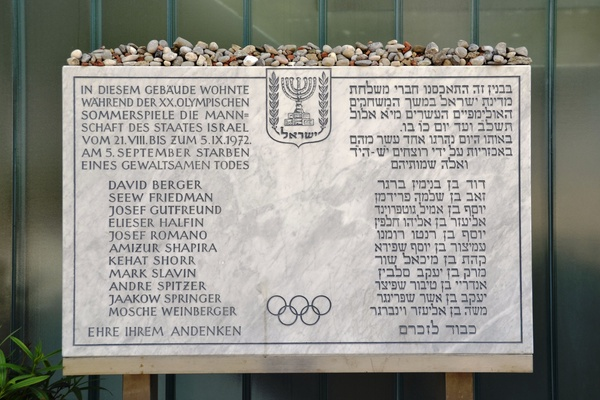 """Tablica pamiątkowa w wiosce olimpijskiej w Monachium. Inskrypcja na tablicy głosi: """"Reprezentacja Izraela mieszkała w tym budynku podczas 20. Letnich Igrzysk Olimpijskich od 21 sierpnia do 5 września 1972. 5 września [lista ofiar] zmarło śmiercią tragiczną. Cześć ich pamięci."""" Fot. High Contrast, [CC BY 3.0](https://creativecommons.org/licenses/by/3.0/pl/)"""