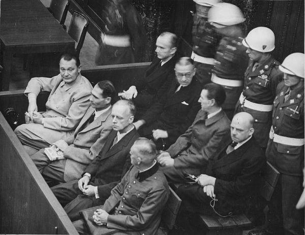 Trybunał Wojskowy w Norymberdze, ława oskarżonych. Od lewej w pierwszym rzędzie: Göring, Hess, Ribbentrop, Keitel, w drugim rzędzie: Dönitz, Raeder, Schirach, Sauckel (domena publiczna)